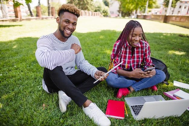 草原で勉強している若い学生