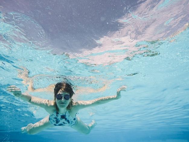 プールでダイビングするゴーグルを持つ女性