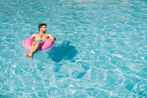 プールのインフレータブルリングで寒い男