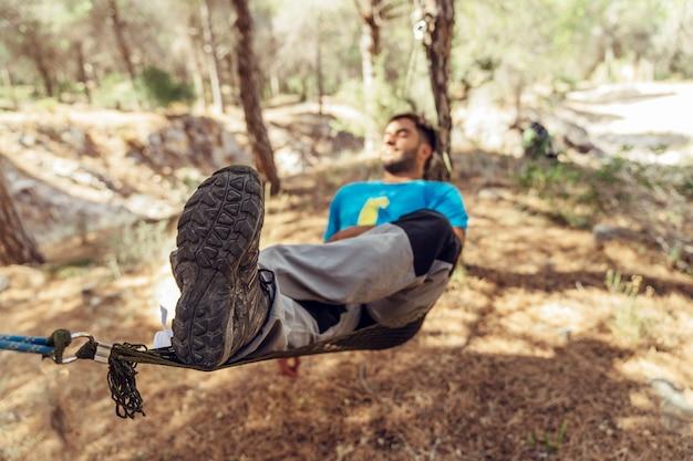 森のハンモックで眠っている男