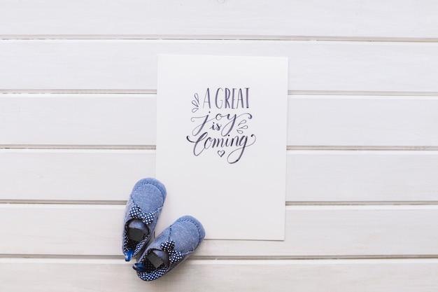 Концепция новорожденного с бумагой и обувью