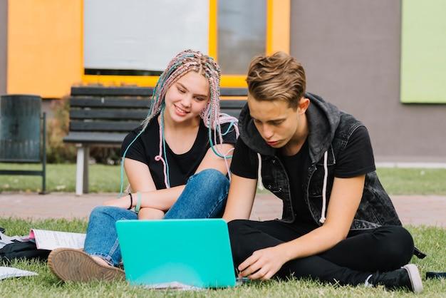 公園で勉強中の若いカップル