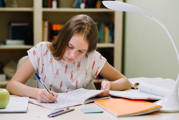 女子学生の座って、書く