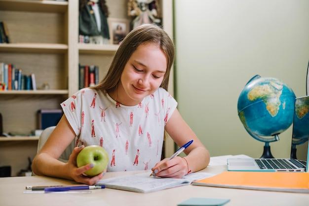 宿題をしているスナックを持つコンテンツの少女