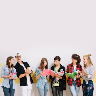 Дети, обучающиеся с книгами на стене