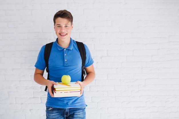 Счастливый мальчик подросток и куча учебников