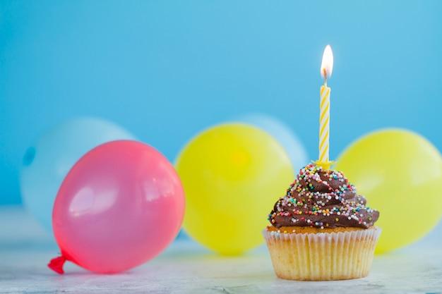 お祝いのカップケーキとカラフルな風船