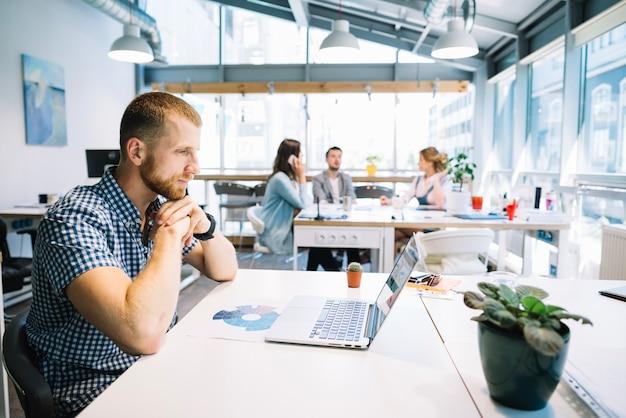 Человек, сидящий на ноутбуке в офисе