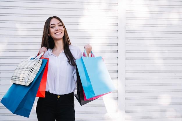 通りで買い物袋を持つ満足のいく女の子