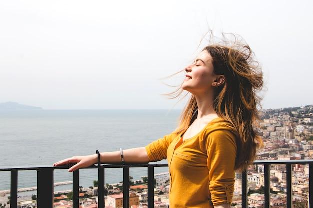 Женщина, наслаждаясь дыханием ветра