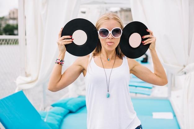 Женщина с виниловыми пластинками, показывающая язык