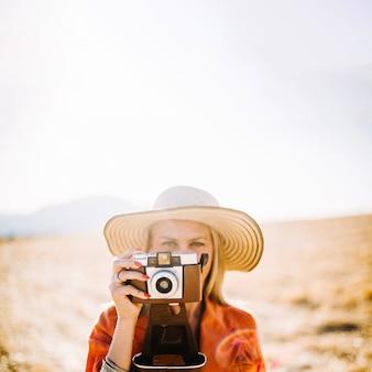 旅行中に古いカメラを使用している自信のある女性