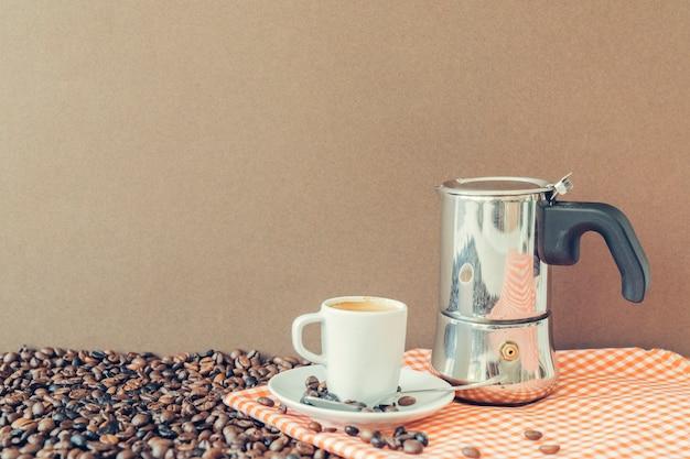 Концепция кофе с горшком мока и эспрессо на ткани