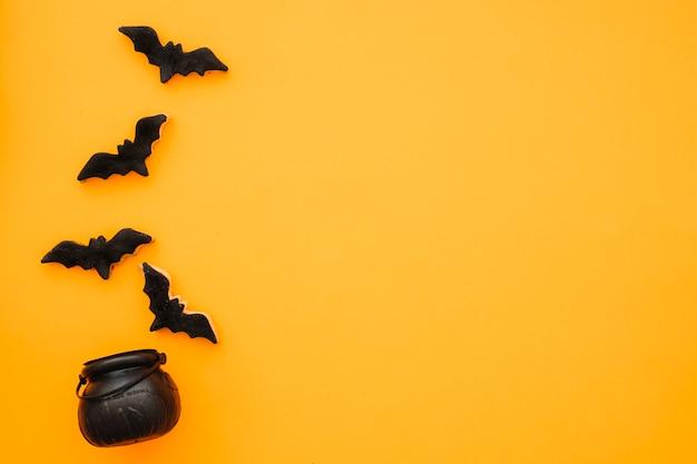 コウモリと茶のポットを持つハロウィンのコンポジション