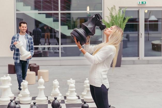 Девушка целует шахматную лошадь по шахматной доске