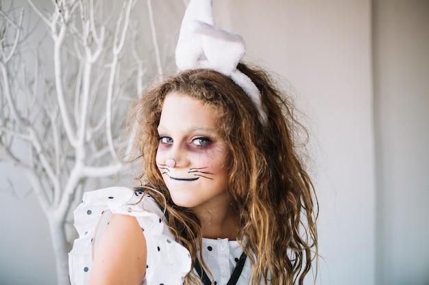 ウサギの顔のペイントでポーズを取っている十代の少女