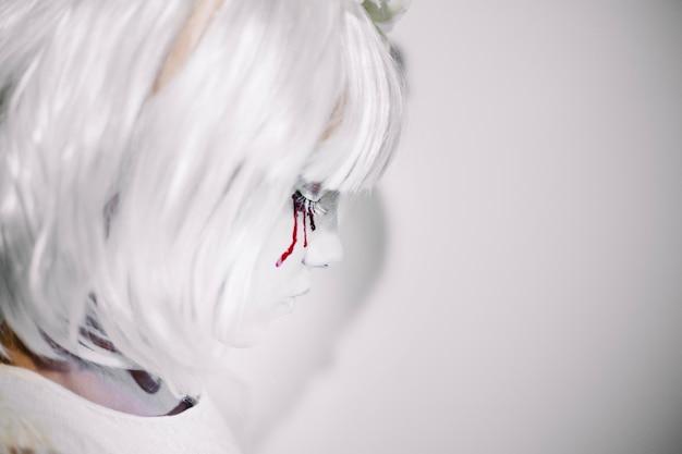 白い顔とかつらを持つ少女