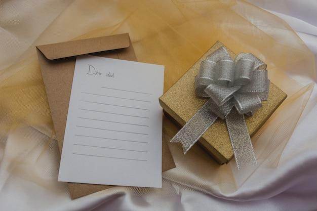 Композиция дня отца с подарком и бумагой для написания сообщения