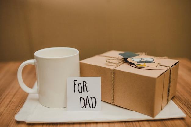 Поверхность с подарком отца и кружкой