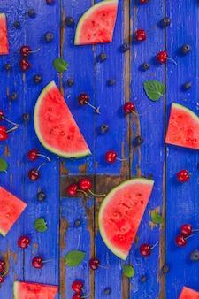 青い木の表面にスイカの部分と他の果物