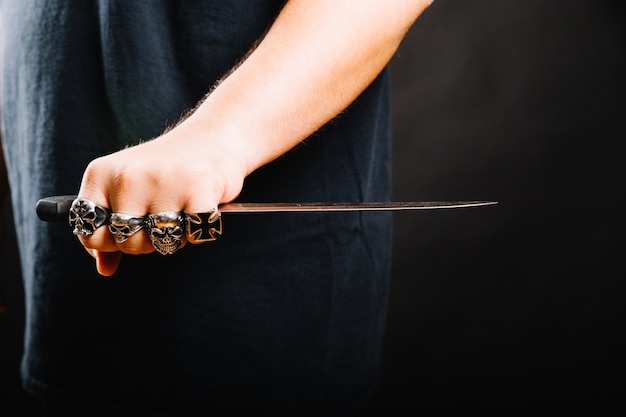 鋭い短剣を持つ男性の手