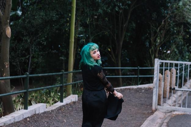 公園に沿って歩く若い女性