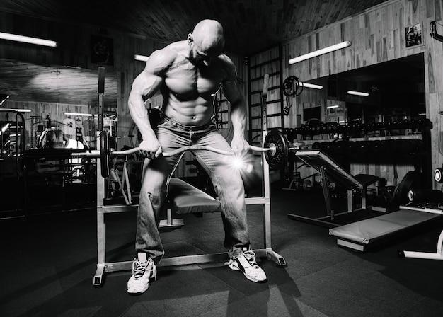 ジーンズで禿げた男性が重いバーベルを持ち上げる