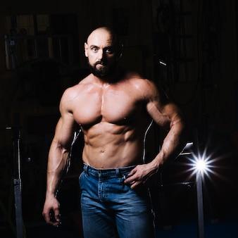 Мышечный человек позирует для камеры