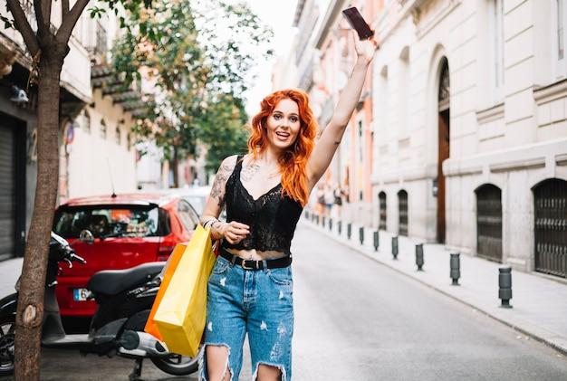 Рыжеволосая женщина, приветствующая такси