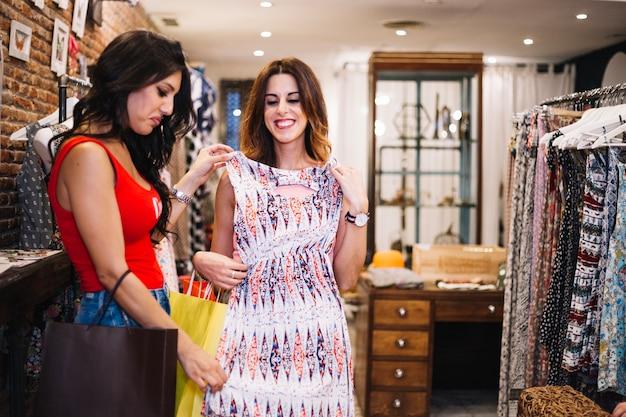 Женщина смотрит на платье критически