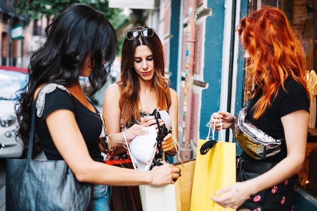 Женщины, показывающие друг другу купленные вещи