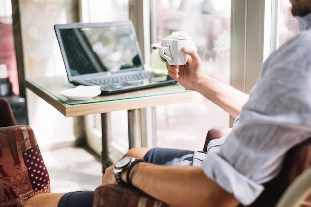 Человек урожая с чашкой кофе в кафе