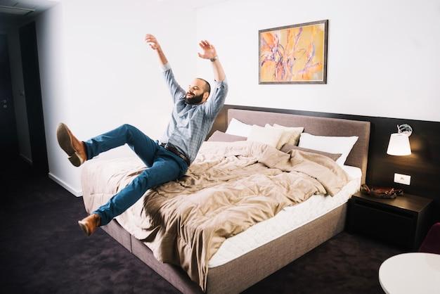 幸せな男がベッドに落ちる