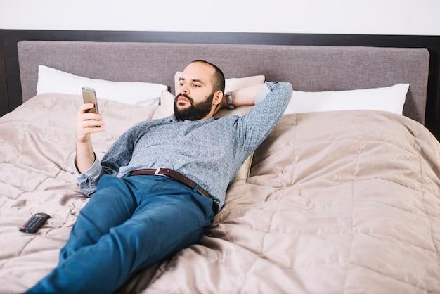 電話でベッドに横たわっているスタイリッシュな男