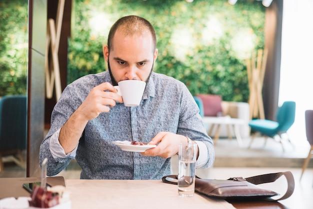 カフェテリアでコーヒーを飲む、不快な男