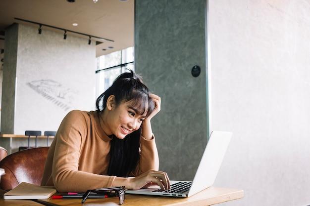 Азиатская женщина, используя ноутбук