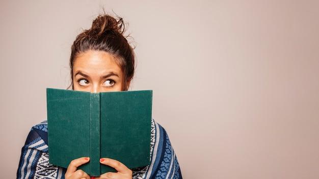 女の子が顔の前で本を持っている