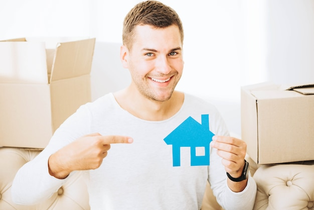 Улыбающийся человек, указывая на бумажный дом