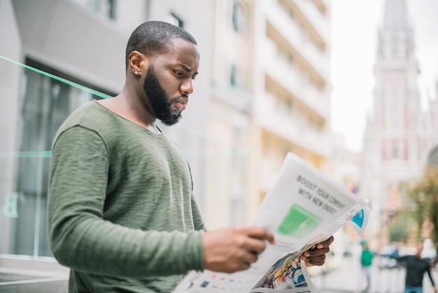通りで新聞を読む男