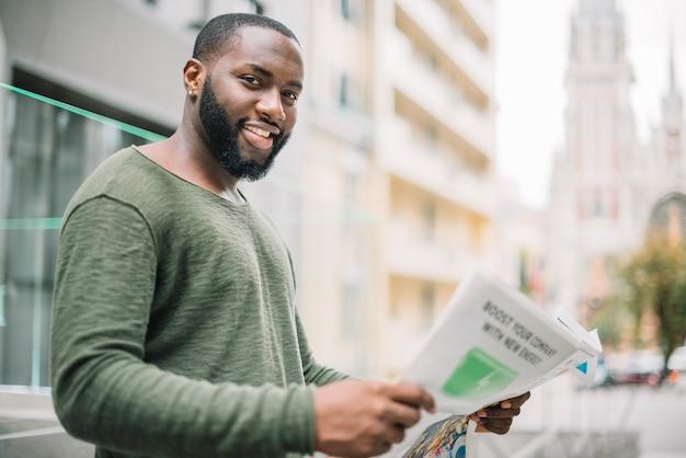 Улыбающийся человек, читающий газету на улице