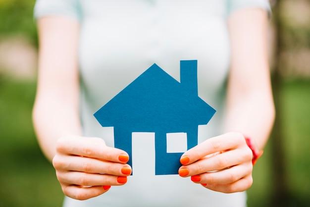 青い切り抜きの家を持つ女性