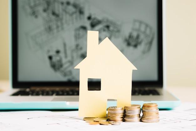 Желтый бумажный дом и монеты на ноутбуке