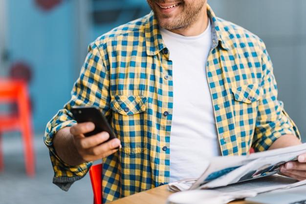 スマートフォンと新聞付きチェッカーシャツの男