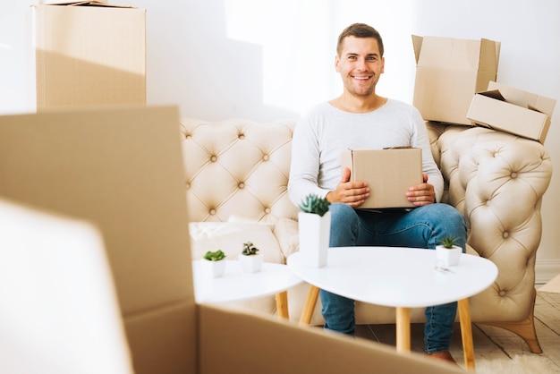 Веселый человек в квартире с коробками