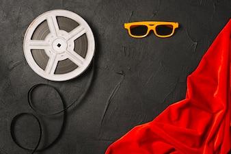 フィルムリールと赤い布の近くの眼鏡