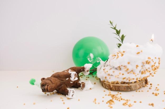 ケーキと風船の近くに横たわっている熊像