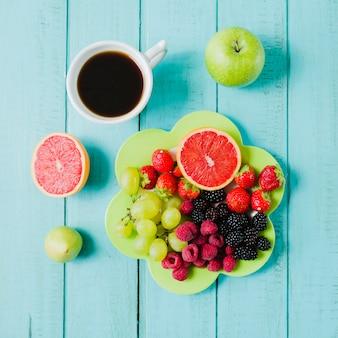 Плита с ягодами и чашкой кофе