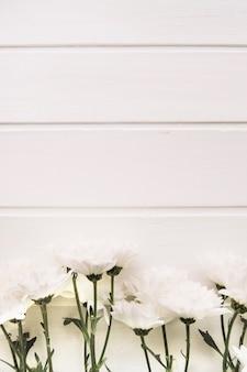 白い木の背景の垂直の前に花