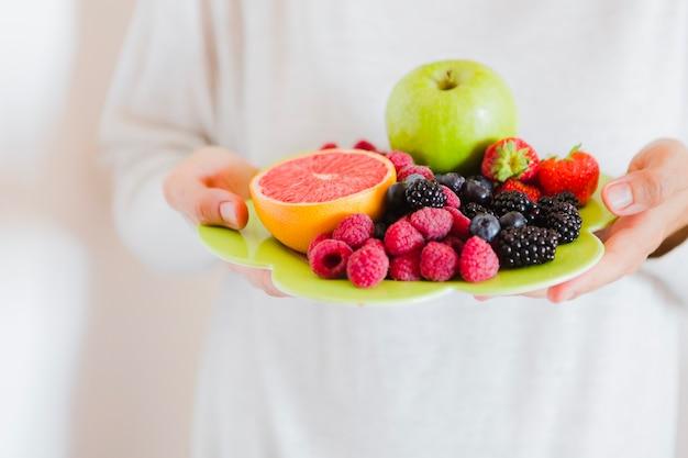 Человек урожая, показывающий плиту с фруктами