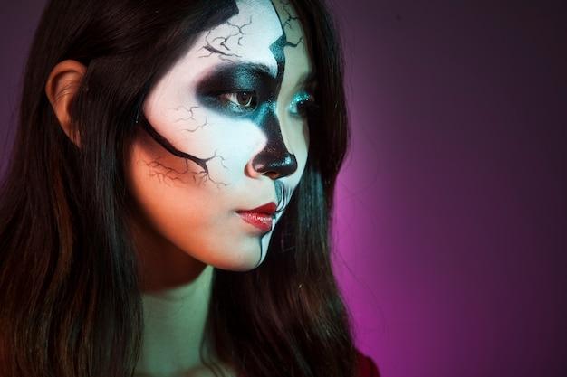 メイクアップ、ハロウィンマスクを持つ女の子の側面図